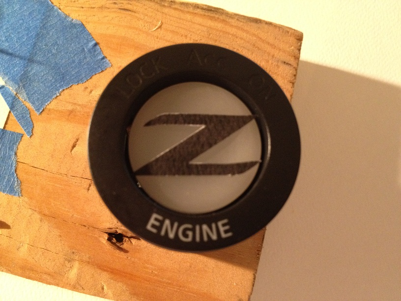 Z logo cut out placed on button inside housing